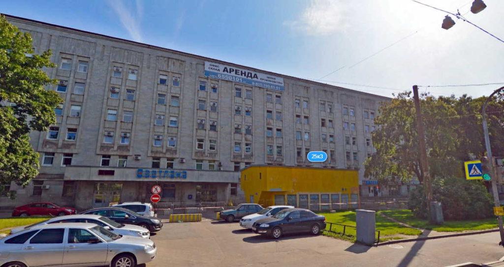 """Изображение завода """"Светлана"""". Перед зданием стоянка автомобилей и деревья."""
