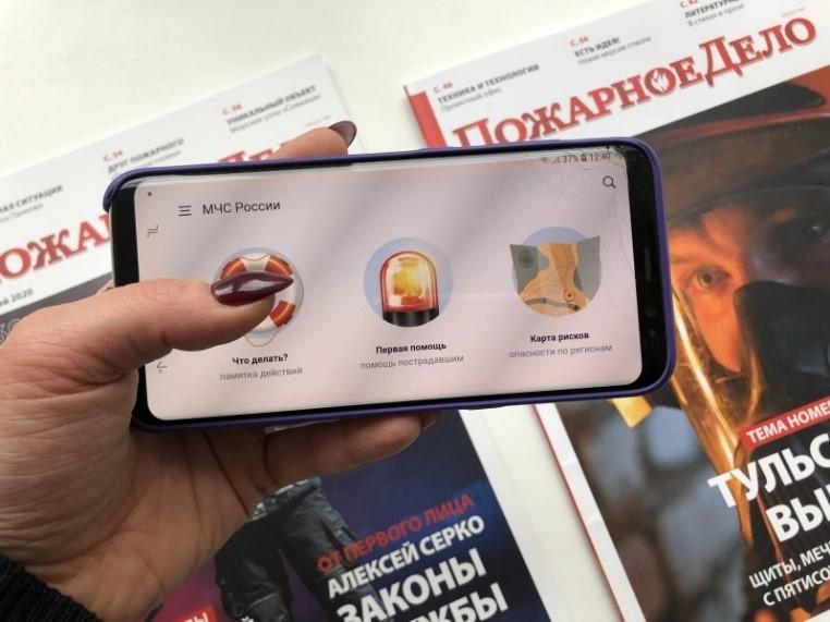 Изображение телефона в руках на фоне печатных изданий МЧС России