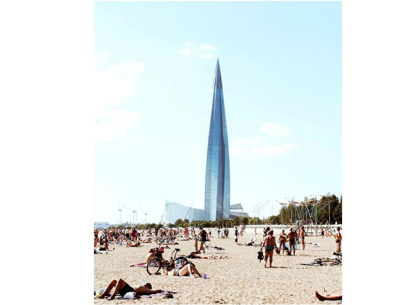 Люди отдыхают на песчаном пляже, на фоне - Лахта-центр