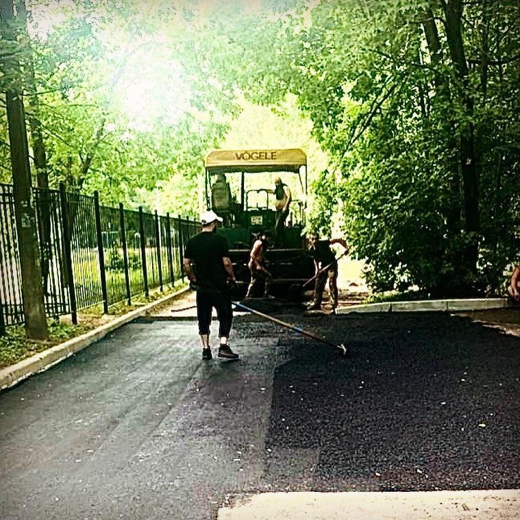 Работает асфальтоукладчик, рабочие разравнивают свежий асфальт. На фоне - зеленые деревья и забор