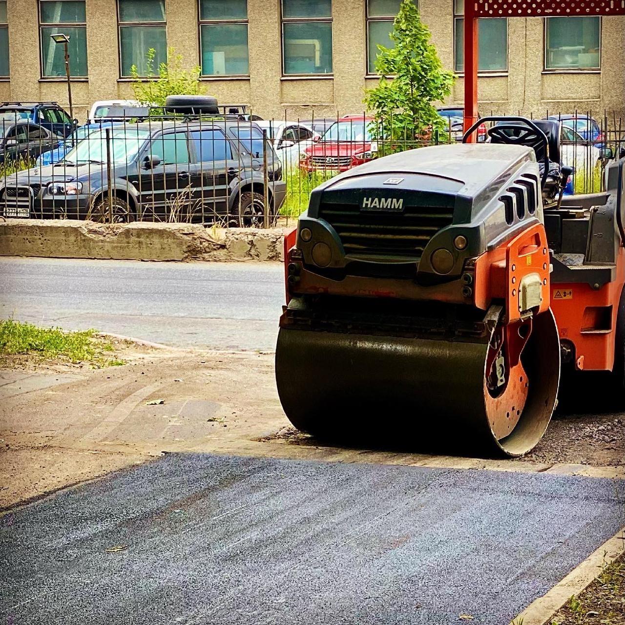 Каток оранжевого цвета закатывает свежий асфальт. На фоне - здание и парковка автомобилей с забором.
