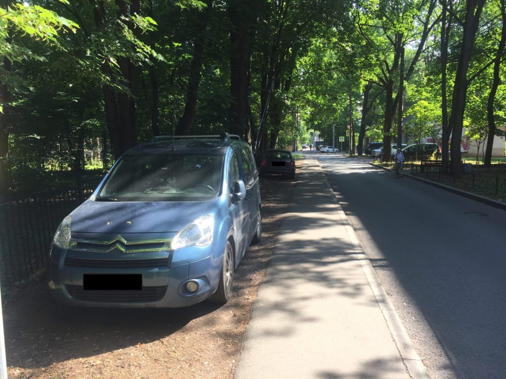 Синий автомобиль припаркован на месте газона
