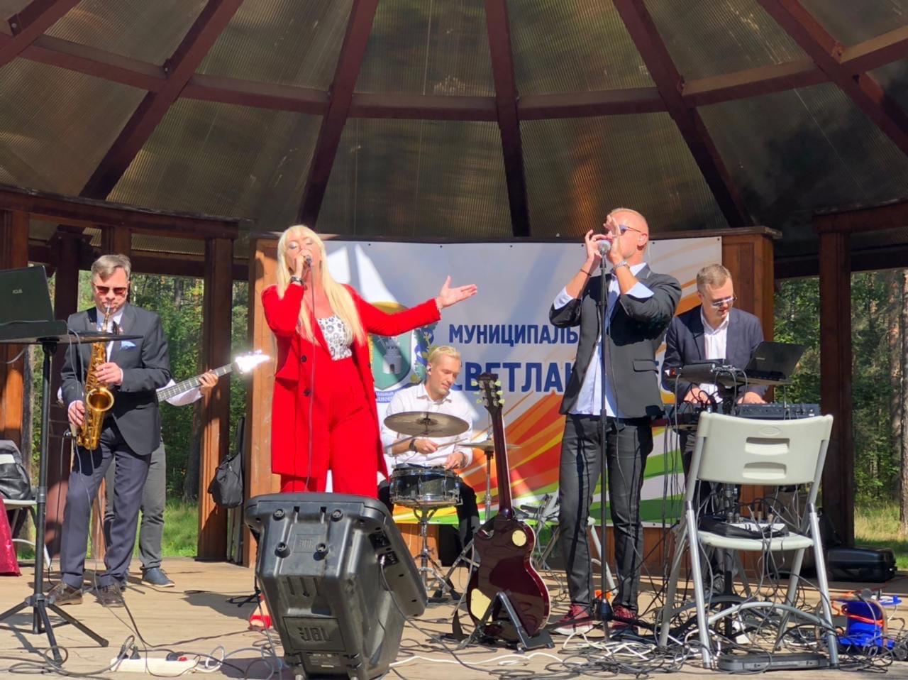 """Музыкальный коллектив на крытой навесом сцене: солистка поёт в красном брючном костюме, справа от неё - мужчина в костюме поёт в микрофон. Позади по центру - барабанщик, слева мужчина в костюме играет на саксофоне, справа мужчина в костюме играет на синтезаторе. На фоне сзади - плакат """"Муниципальное образование Светлановское""""."""