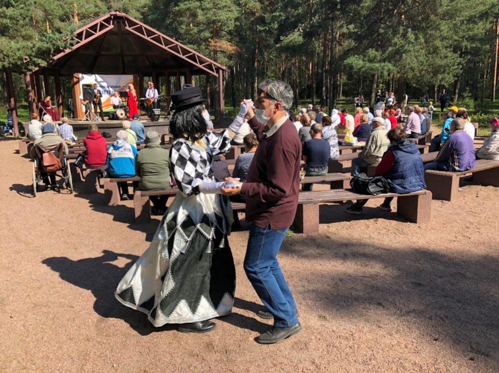 Мужчина и женщина (аниматор в черно-белом платье в ромбик и шляпе) танцуют. На фоне - сцена с музыкантами и люди сидящие на скамейках (смотрят и слушают выступающую группу музыкантов). На заднем плане - хвойный лес.
