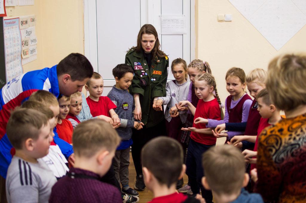 Представители Студенческих отрядов стоят в кругу взявшись за руки с детьми начальных классов школы