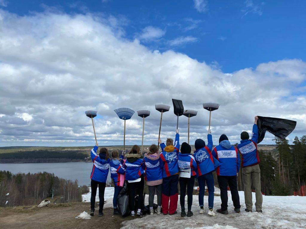 9 представителей Студенческих отрядов стоят на берегу реки на снегу, подняв в руки грабли, лопаты и мусорные мешки