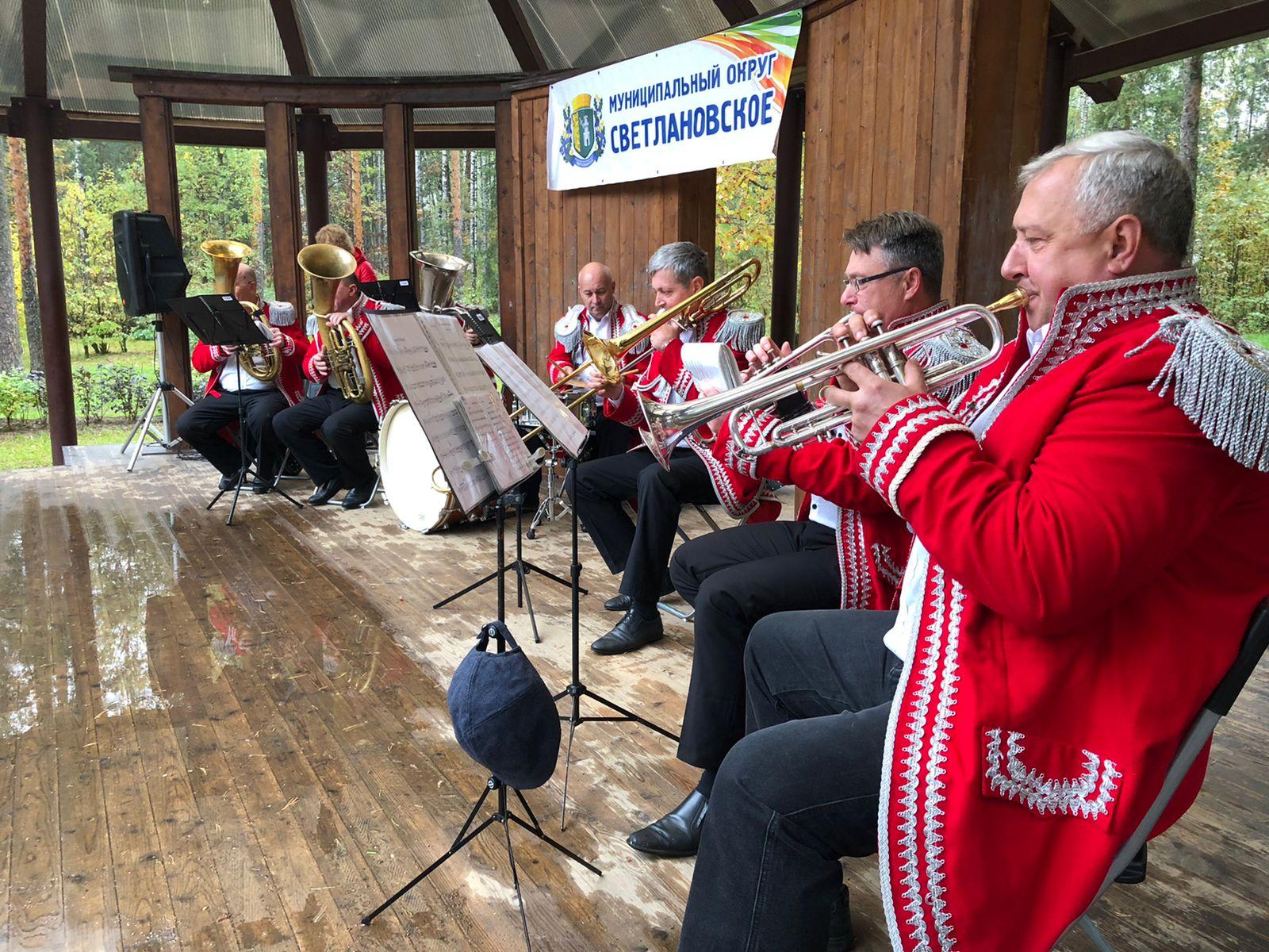 Музыканты духового оркестра играют на сцене в парке Сосновка в красных пиджаках 25.09.2021