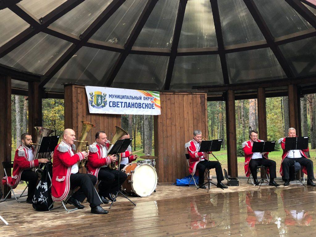 Музыканты духового оркестра играют на сцене в парке Сосновка 25.09.2021 в красных пиджаках