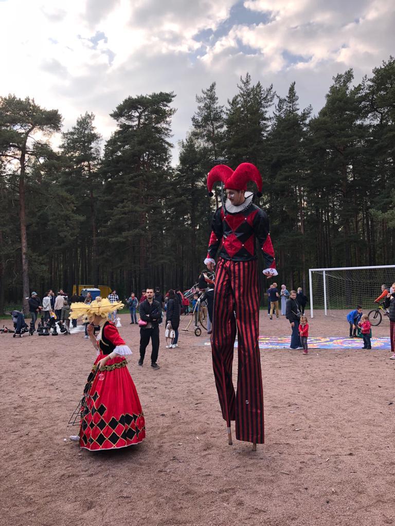 Человек на ходулях в красном костюме в парке  Сосновка