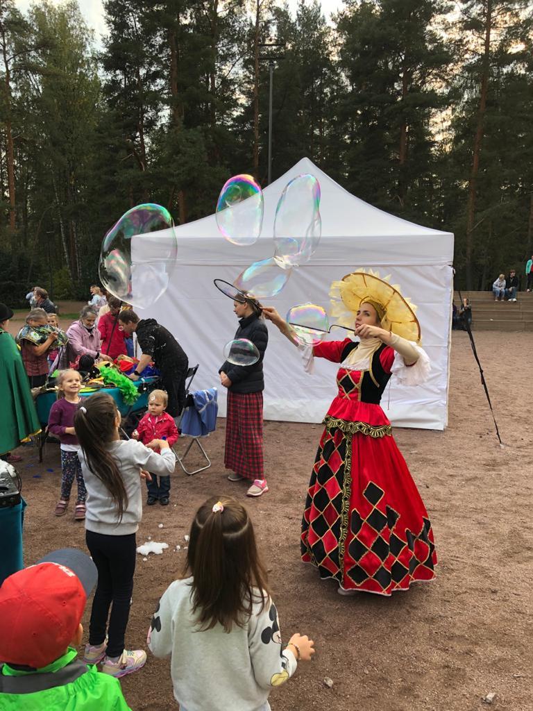 Женщина показывает шоу мыльных пузырей для детей