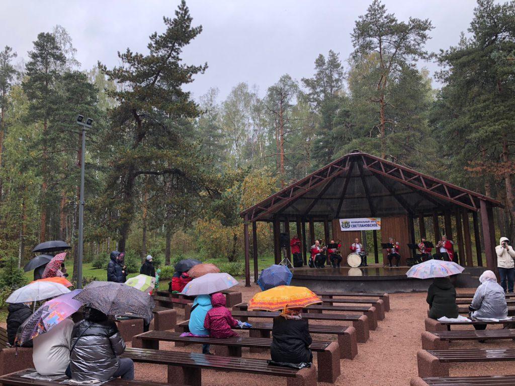 Жители МО Светлановское слушают концерт духового оркестра в парке Сосновка 25.09.2021. У всех в руках зонтики, идет дождь.