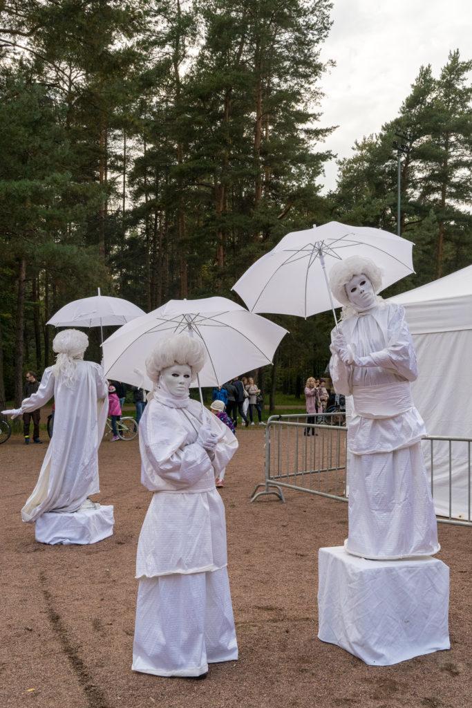 Жители МО Светлановское на концерте в парке Сосновка. На фоне - живые статуи