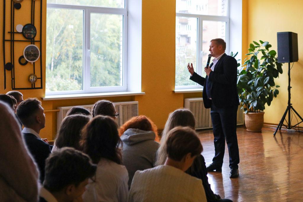 Выступление ведущего мероприятия - мужчина в черном костюме и белой рубашке. на фоне - школьники слушают  и смотрят на ведущего.