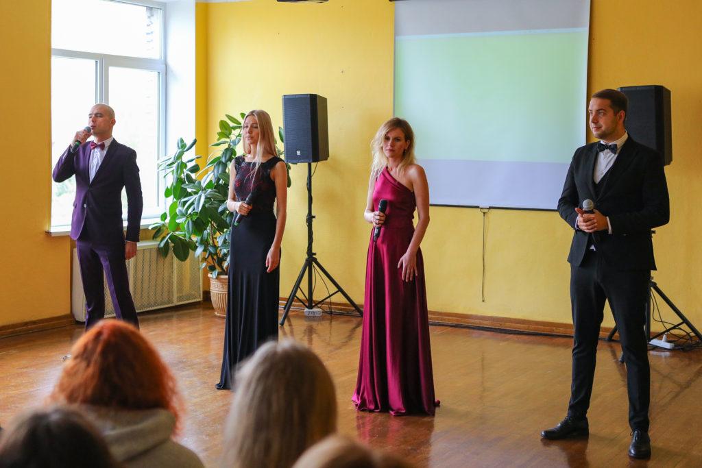 Вокальный коллектив - посередине 2 девушка, одна в черном классическом платье в пол, другая в бардовом платье в пол. По бокам - 2 мужчины, слева мужчина поет в микрофон в темно-бардовом костюме, белой рубашке и бардовой бабочке. Слева  мужчина в черном костюме, белой рубашке и черной бабочке. На фоне на желтой стене - проектор, колонки и зеленый цветок в горшке.