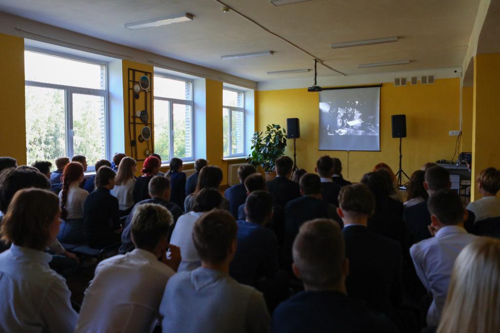 Школьники смотрят фильм, посвященный Дню солидарности в борьбе с терроризмом. На фоне на желтой стене - экран (на экране идет фильм) и проектор, колонки, на столе - ноутбук и диджейское оборудование.