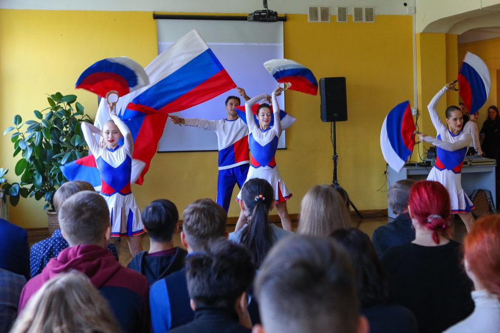 Выступление коллектива - 3 девушки и парень в форме цветов российского флага (белый, синий и красный) выполняют различные танцевальные движения с помощью реквизитов в форме больших вееров в цветах российского флага.