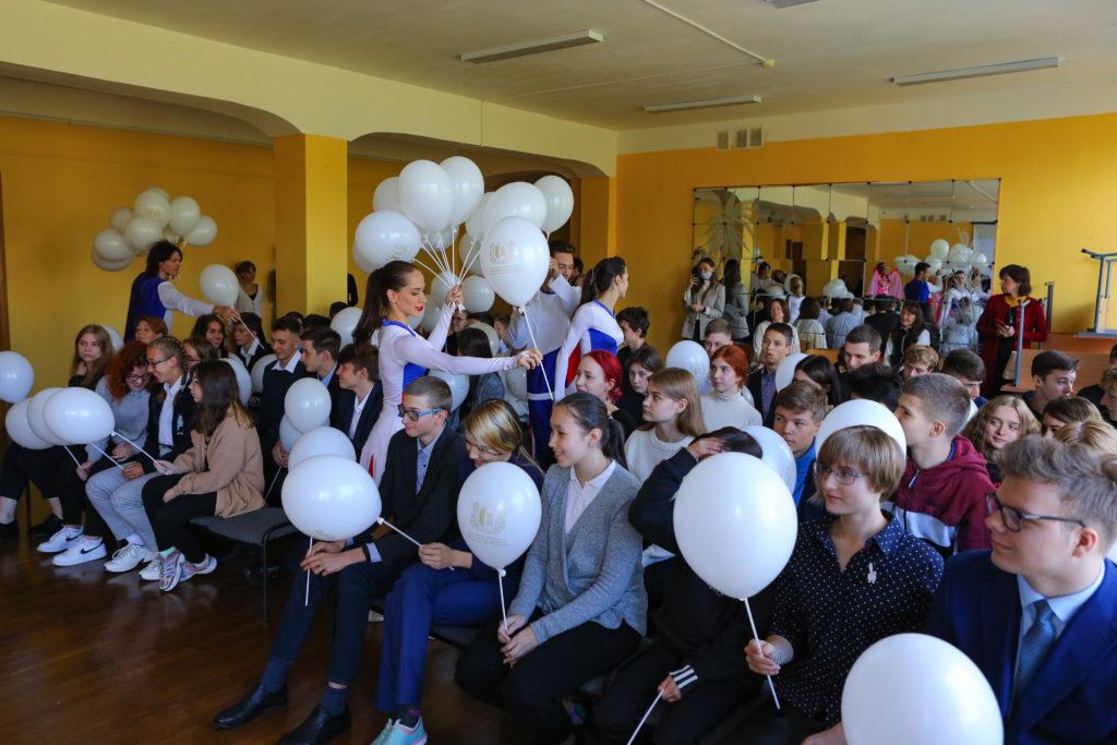 Участники выступлений мероприятия (девушки в одежде цветов российского флага - белый, синий и красный) раздают школьникам белые шары на палочках. На фоне - большое настенное зеркало и парты.