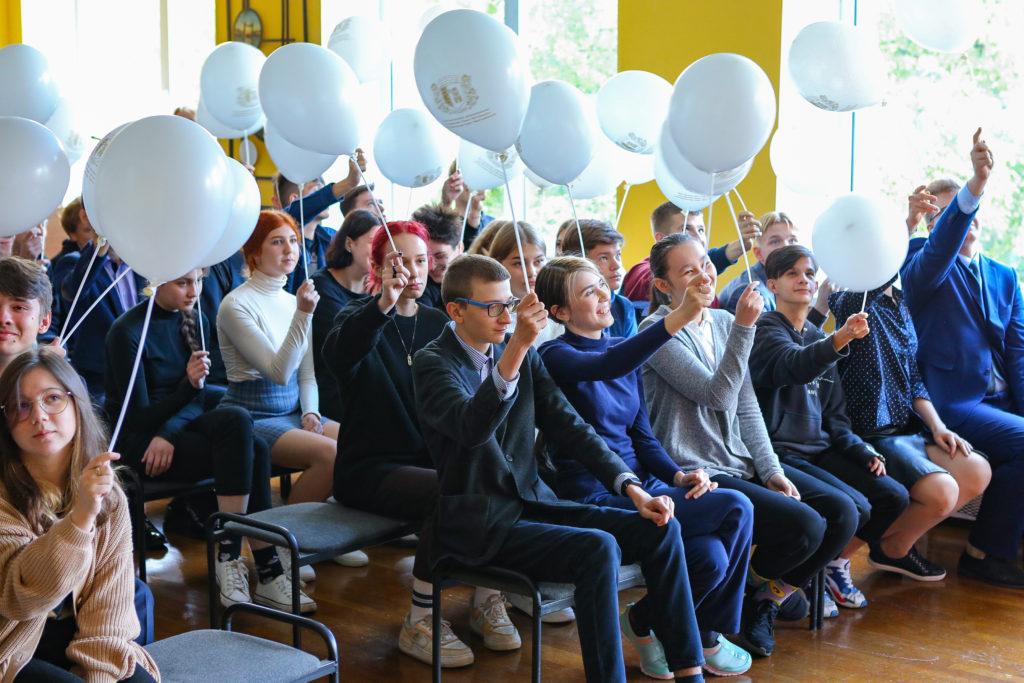Школьники подняли белые шары на палочках вверх над собой.