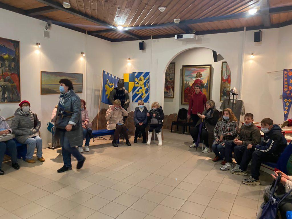 """Жители МО Светлановское на экскурсии в музее-диораме """"Невская битва 1240 года"""". Люди сидят на скамейках, на стенах висят различные картины, изображающие воинов и пейзажи. Вдоль стен расположены: кольчужный костюм (броня) шведского рыцаря, на фоне флаги и щит цветов шведского флага (синий и желтый) с изображениями львов желтого (золотого) цвета."""