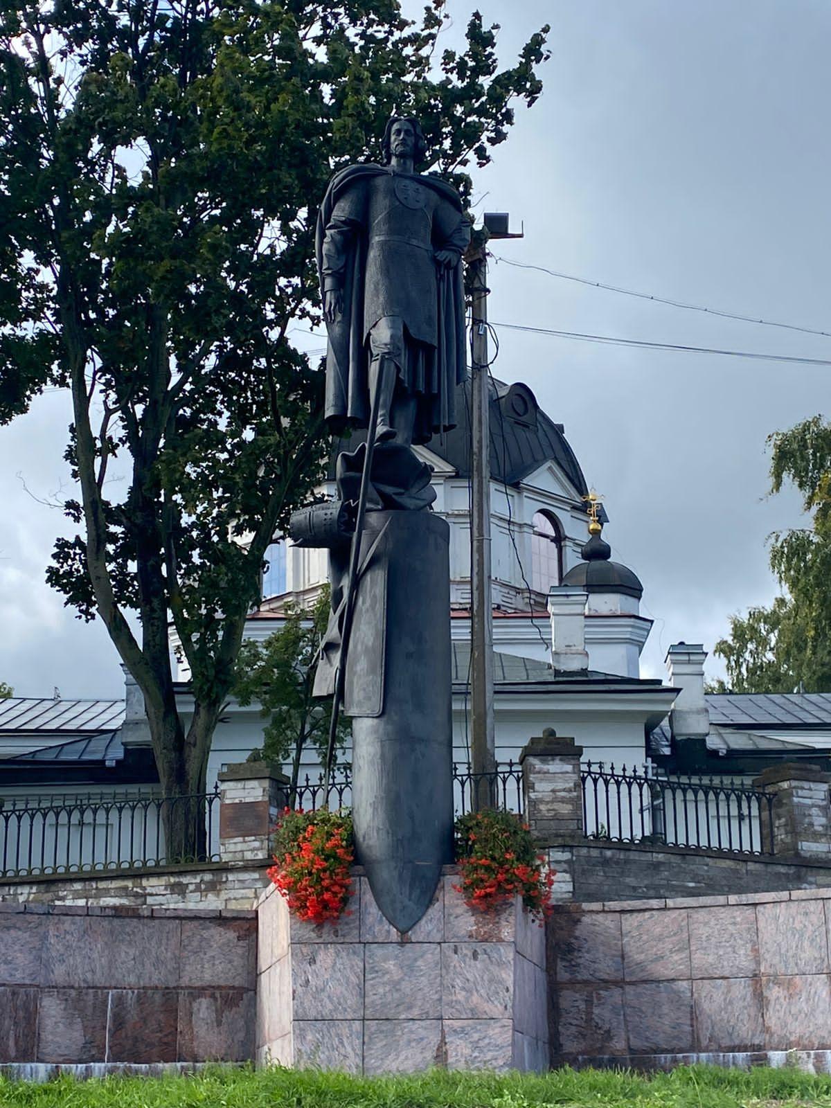 Памятник Святого благоверного князя Александра Невского в Усть-Ижоре - князь изображен в кольчуге и плаще, поставив ногу на обмундирование шведского воина. На фоне - церковь и зеленые деревья.