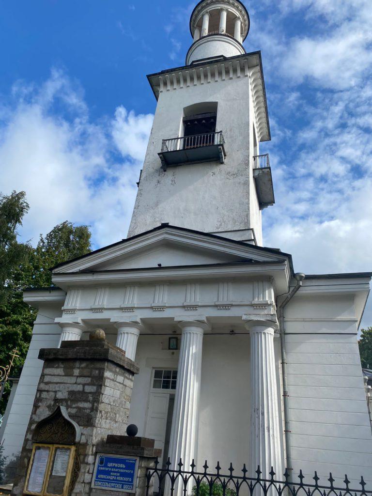 Церковь Святого благоверного князя Александра Невского в Усть-Ижоре - высокая белая церковь с балкончиками на колокольне и колоннами при входе в церковь.