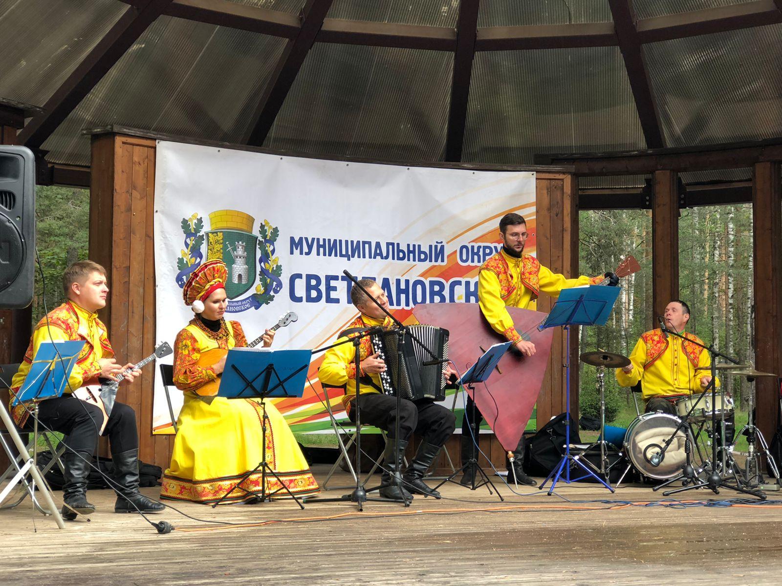 На летней эстраде (сцене с навесом) в парке Сосновка (на фоне деревья и кустарники) играют музыканты (5 человек в русских народных костюмах: желтые рубашки с оранжевыми нашивками, черные штаны) на музыкальных инструментах. По бокам и по центру колонки.