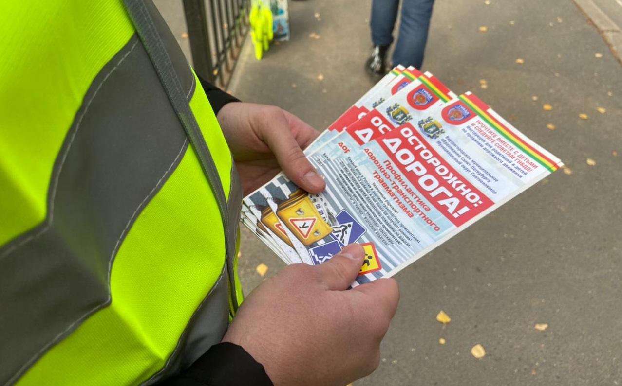 """Человек в зеленом светоотражающем жилете держит в руках брошюры МО Светлановское """"Осторожно: дорога!"""""""