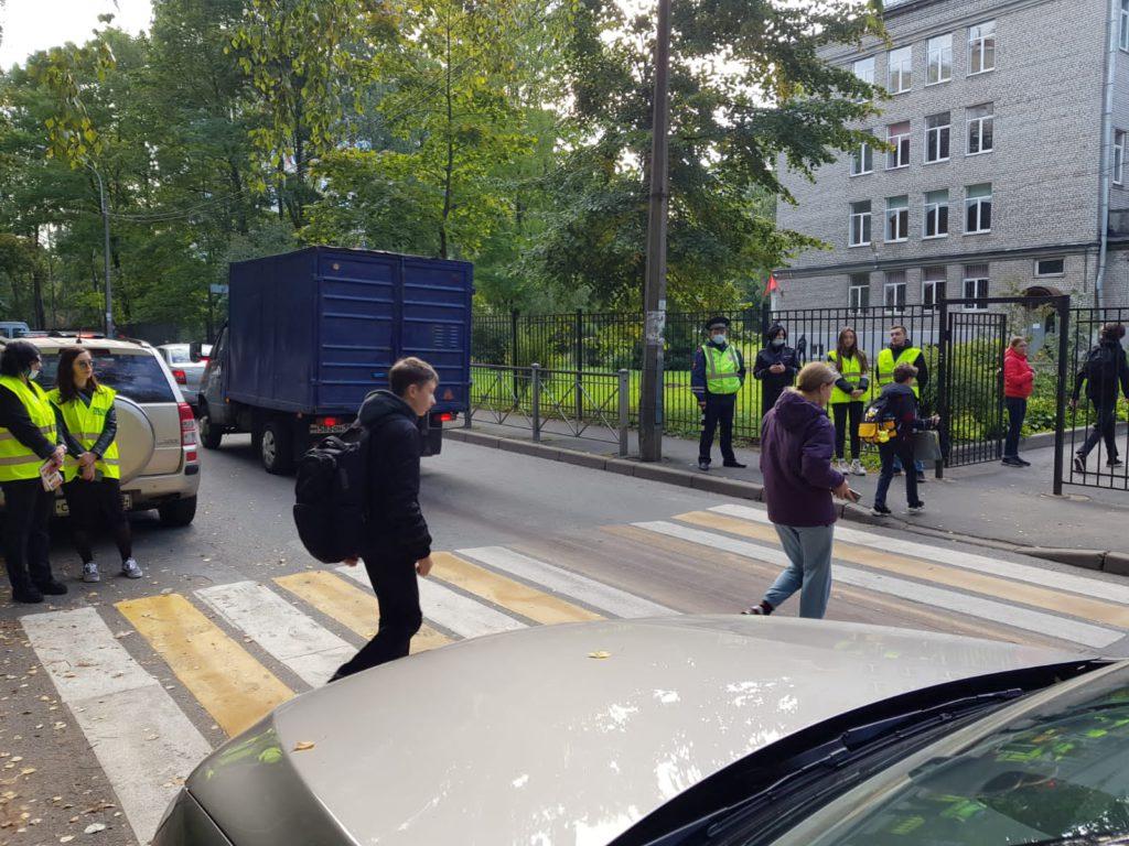 Пешеходный переход на дороге, ведущий к школе.  На обочинах и на проезжей части стоят автомобили (автомобиль бежевого цвета и газель синего цвета). По пешеходному переходу идут 2 человек - школьник с портфелем в черных куртке и штанах и женщина в синих штанах и фиолетовой куртке. По сторонам от проезжей части на тротуарах стоят организаторы мероприятия в зеленых светоотражающих жилетах, а также 2 сотрудника ГИБДД в синей форме, фуражках. У одного из представителей ГИБДД в руках черно-белый жезл.