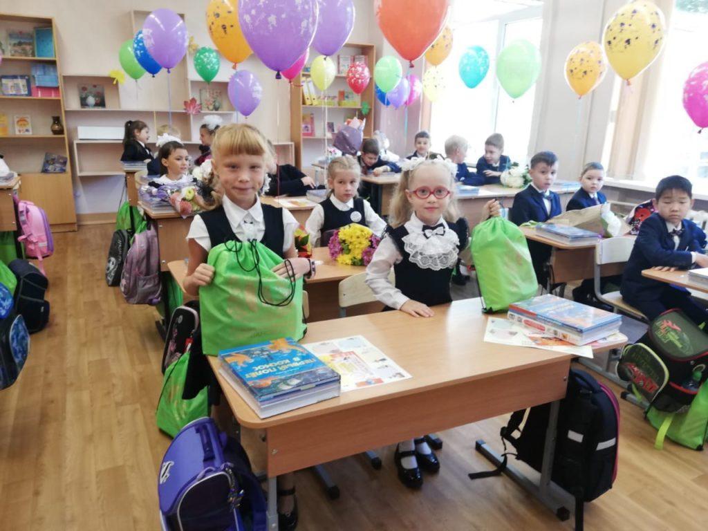 На фото в классной комнате школы изображены дети (первоклассники), сидящие за партами. На партах брошюры и учебники, а также ранцы и спортивные сумки зеленого цвета с подарками от МО Светлановское. За стулья привязаны разноцветные гелиевые шары.