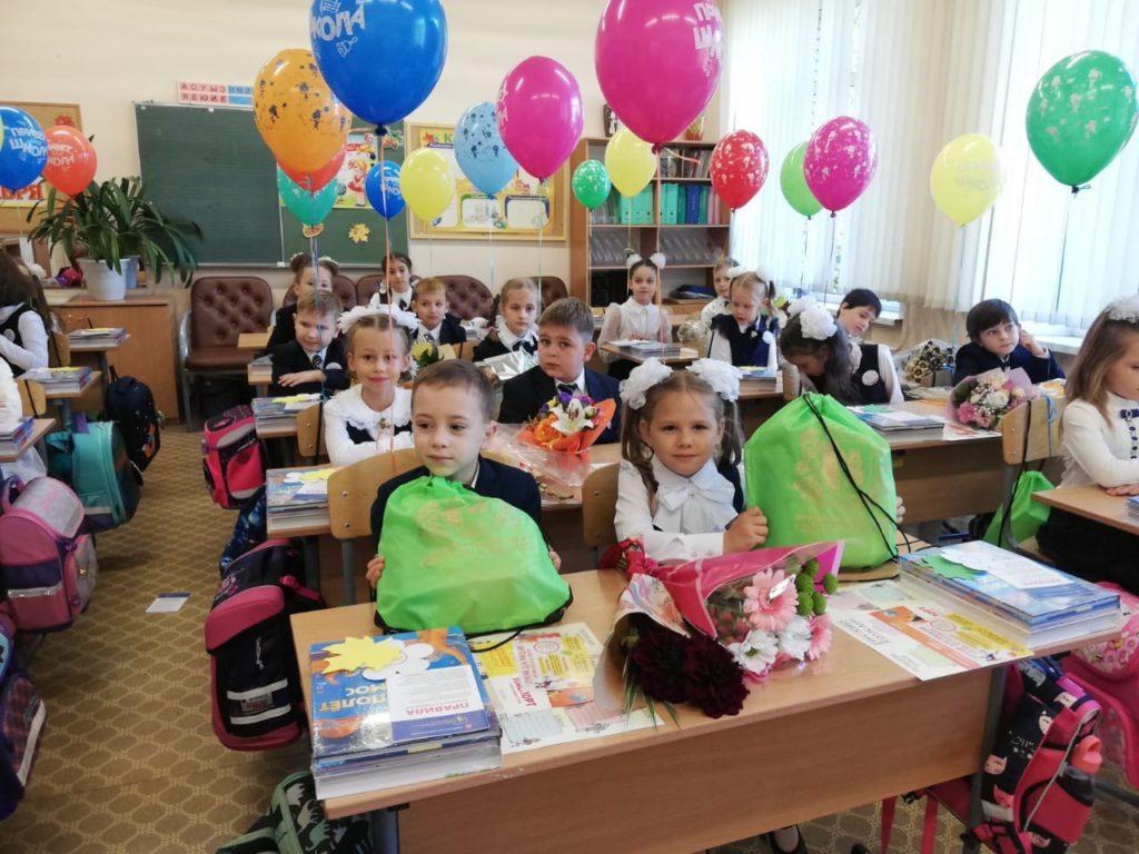 На фото в классной комнате школы изображены дети (первоклассники), сидящие за партами. На партах брошюры и учебники, а также цветы, ранцы и спортивные сумки зеленого цвета с подарками от МО Светлановское. За стулья привязаны разноцветные гелиевые шары.