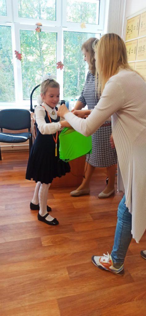 В классной комнате в школе 2 учителя вручаются подарок от муниципального округа Светлановское (зеленую спортивную сумку с подарками внутри) девочке (первокласснице).